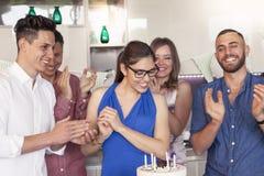 Jolie fille avec le gâteau d'anniversaire entouré de ses amis Photographie stock libre de droits