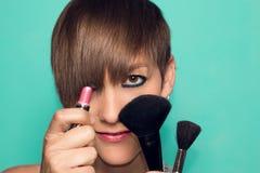 Jolie fille avec le maquillage et les accessoires de maquillage Rouge à lèvres, applicateur de maquillage image stock