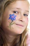 Jolie fille avec le renivellement de guindineau de fleur Image stock