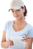 Jolie fille avec le sourire de tablette et d'earbuds Images stock