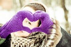Jolie fille avec les mains en forme de coeur dans les gants photographie stock