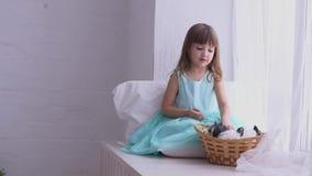 Jolie fille ayant l'amusement, étreignant et jouant avec le lapin décoratif banque de vidéos