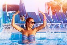 Jolie fille ayant l'amusement dans la piscine Photos libres de droits