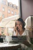 Jolie fille ayant la tasse de café et lisant le journal Photo stock