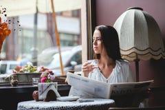 Jolie fille ayant la tasse de café et lisant le journal Photographie stock