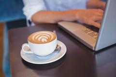 Jolie fille ayant le café utilisant l'ordinateur portable Photos stock