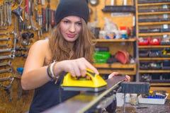 Jolie fille cirant le ski dans l'atelier photographie stock libre de droits