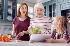 Jolie fille démontrant la recette de salade à la mère et à la grand-mère Image stock
