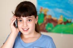 Jolie fille d'école employant le mobile Image libre de droits
