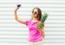 Jolie fille dans des lunettes de soleil avec l'ananas prenant le selfie de photo sur le smartphone Images stock