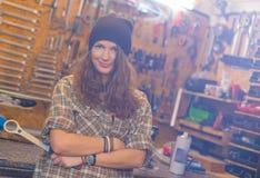 Jolie fille dans l'atelier avec un outil photos stock