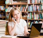Jolie fille dans la bibliothèque dactylographiant sur l'ordinateur portable et parlant au téléphone Photographie stock libre de droits