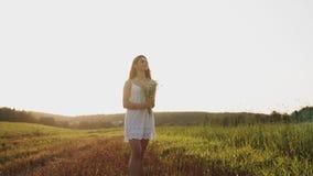 Jolie fille dans la robe blanche se tenant dans le domaine avec le bouquet des fleurs, regardant le ciel clair de soirée banque de vidéos
