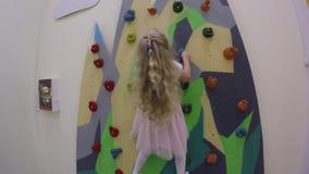 Jolie fille dans la robe rose s'élevant sur le mur de roche dans à l'intérieur le terrain de jeu banque de vidéos