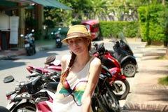Jolie fille dans le chapeau Sourire sur le fond de motocyclettes Photographie stock libre de droits