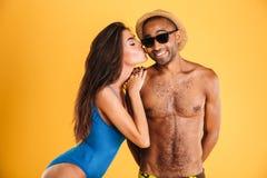 Jolie fille dans le maillot de bain embrassant son ami africain Photographie stock
