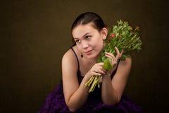 Jolie fille dans le pourpre avec des fleurs Photos stock