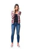 Jolie fille dans les jeans et des espadrilles parlant au téléphone portable ajustant des cheveux Images libres de droits