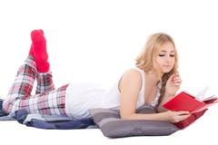 Jolie fille dans les pyjamas se trouvant et le livre de lecture d'isolement sur le blanc Photos libres de droits