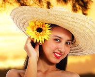 Jolie fille dans un chapeau au coucher du soleil Image stock