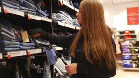 Jolie fille dans un essai de mail pour trouver une bonne paire de jeans banque de vidéos
