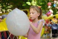 Jolie fille dans une robe tenant la sucrerie de coton à la foire photos libres de droits