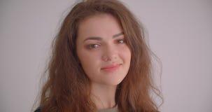 Jolie fille de brune aux tours de veste en cuir à la caméra et aux sourires joli d'isolement sur le fond blanc banque de vidéos