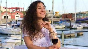 Jolie fille de brune avec un verre de vin rouge banque de vidéos