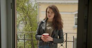 Jolie fille de brune dans la position de veste en cuir sur le balcon avec la vue verte de ville et le thé chaud potable étant rêv banque de vidéos