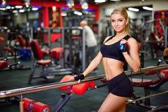 Jolie fille de forme physique tenant une corde de saut dans le gymnase, regardant la droite, le fond admirablement brouillé Image stock