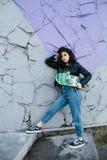 Jolie fille de l'adolescence passant le temps en parc près de l'eau avec son patin Photo stock