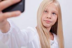 Jolie fille de l'adolescence prenant des selfies avec elle futée image stock