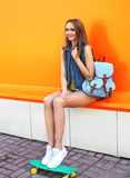 Jolie fille de mode avec la planche à roulettes et le sac à dos Photos libres de droits