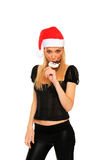 Jolie fille de Noël mangeant une sucrerie de bonhomme de neige Photographie stock libre de droits
