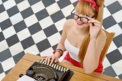 Jolie fille de pin-up avec la vieille machine à écrire image stock