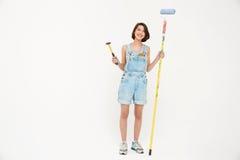 Jolie fille de portrait intégral, tenant le marteau et peignant le RO Images stock