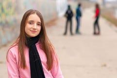 Jolie fille de sourire posant à l'extérieur avec des amis Image stock