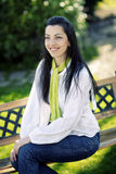 Jolie fille de sourire s'asseyant sur le banc Photos stock