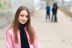 Jolie fille de sourire sur la pose de patins de rouleau extérieure avec des amis Photographie stock