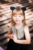 Jolie fille de trois ans dans un costume de chat, avec une fleur dans sa main Photo libre de droits