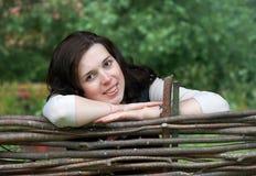 Jolie fille derrière la frontière de sécurité en bois Photos stock
