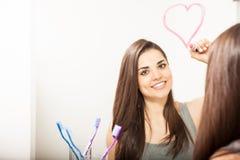Jolie fille dessinant un coeur avec le rouge à lèvres Images libres de droits