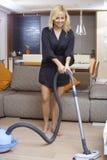 Jolie fille employant l'aspirateur à la maison Photo stock