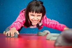 Jolie fille escaladant un mur dans un terrain de jeu Images stock