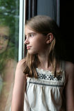 Jolie fille et sa réflexion à l'hublot Image stock
