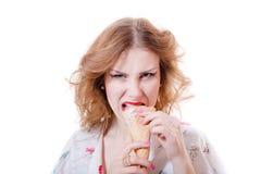 Jolie fille fâchée ou affamée mangeant le cornet de crème glacée regardant l'appareil-photo d'isolement sur le fond blanc Photo libre de droits