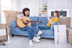 Jolie fille filmant son ami jouant la guitare pour elle Image stock