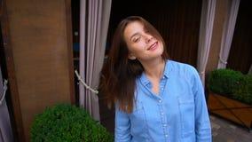 Jolie fille jouant avec des cheveux dans le mouvement lent et regardant l'appareil-photo près du café clips vidéos