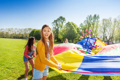 Jolie fille jouant le parachute avec des amis extérieurs Photos libres de droits