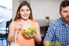 Jolie fille mangeant de la salade avec des amis Photos libres de droits